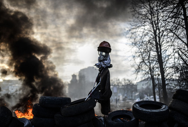 A scarecrow-like mock anti-government protestor is pictured on a barricade between protestors and government forces on February 21, 2014 in Kiev. (Photo by Bulent Kilic/AFP Photo)