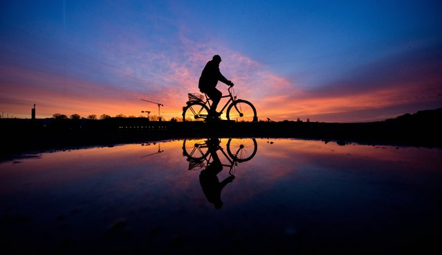 A cyclist is silhouetted against the rising sun and reflected in a puddle in Hannover, northern Germany, Tuesday, February 18, 2014. (Photo by Julian Stratenschulte/AP Photo/DPA)