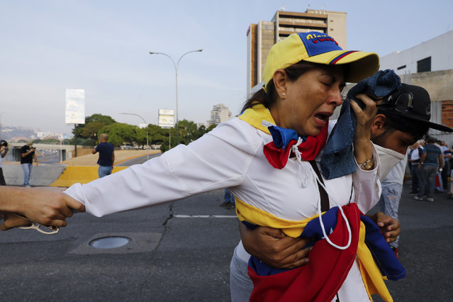 A woman suffocated by tear gas is aid by fellow opponents of President Nicolas Maduro outside La Carlota air base in Caracas, Venezuela, Tuesday, April 30, 2019. (Photo by Ariana Cubillos/AP Photo)