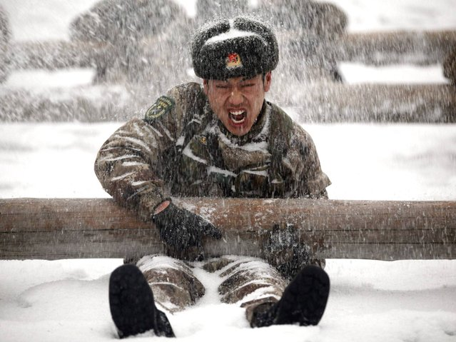 Soldiers take part in a drill during a heavy snow in Heihe, Heilongjiang province, February 26, 2014. (Photo by Reuters/China Daily)