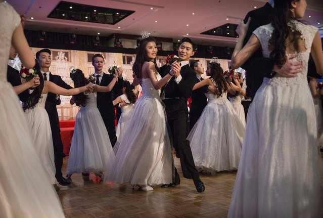 Chinese and foreign debutantes dance during the Vienna Ball at the Kempinski Hotel on March 19, 2016 in Beijing, China. The ball, which is an event organized by the luxury Kempinski Hotel chain and the City of Vienna, brings together both Chinese and foreign members of the capital's elite class. Despite a slowing economy, private wealth has soared in China after decades of rapid growth. (Photo by Kevin Frayer/Getty Images)