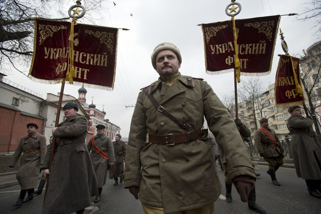 Pro-Kremlin demonstrators dressed in WWII army uniforms and carrying replicas of Soviet Army WWII banners reading, Ukrainian Front, march in central Moscow, Russia, Sunday, March 2, 2014 to express support for the latest developments in Russian-Ukrainian relations. Banners are those of units that were liberating Ukraine from Nazi occupation during WWII. (Photo by Pavel Golovkin/AP Photo)