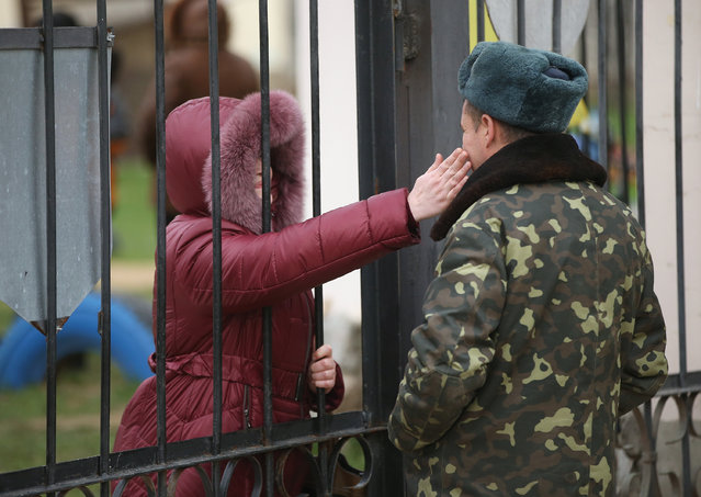A Ukrainian soldier inside the Belbek military base gets an affectionate pet from a woman who was among approximately two dozen who spent the night outside the gate in support of the men on March 3, 2014 in Lubimovka, Ukraine. (Photo by Sean Gallup/Getty Images)