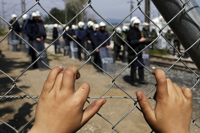 A child places his hands on a fence as Greek police officers stand guard after minor clashes occurred at a makeshift camp for migrants and refugees at the Greek-Macedonian border near the village of Idomeni, Greece, March 29, 2016. (Photo by Marko Djurica/Reuters)