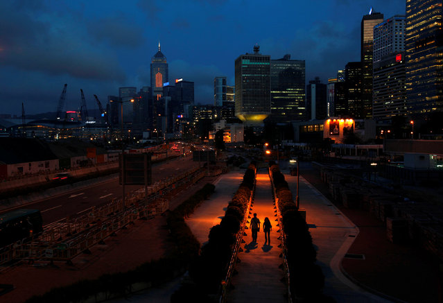 People walk on a pavement at Hong Kong's financial Central district during sunset May 11, 2011. (Photo by Bobby Yip/Reuters)