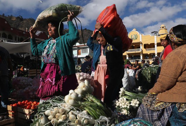 Women carry loads of onions through a vegetable market on February 11, 2017 in Almolonga, Guatemala. (Photo by John Moore/Getty Images)