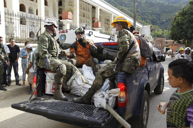Rescue workers arrive at a cemetery carrying the body of a victim, after a landslide in the municipality of Salgar, in Antioquia department, May 19, 2015. (Photo by Fredy Builes/Reuters)