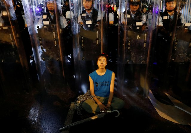 A demonstrator sits down in front of riot police during a demonstration to demand authorities scrap a proposed extradition bill with China, in Hong Kong, China June 12, 2019. (Photo by Tyrone Siu/Reuters)