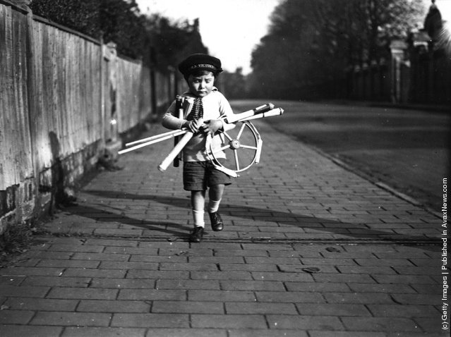 A young boy carrying home a selection of fireworks, 1925