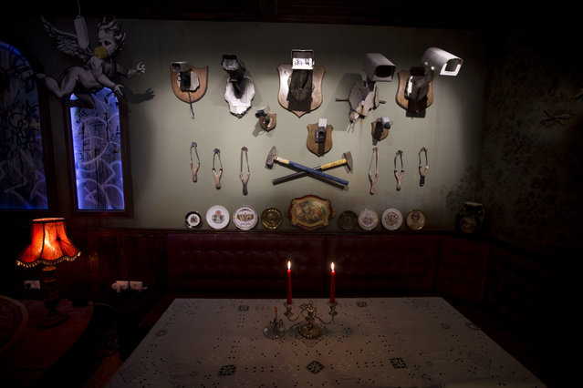 "A wall decorated with security cameras and slingshots is seen in the bar area of the ""The Walled Off Hotel"" and the Israeli security barrier in the West Bank city of Bethlehem, Friday, March 3, 2017. (Photo by Dusan Vranic/AP Photo)"