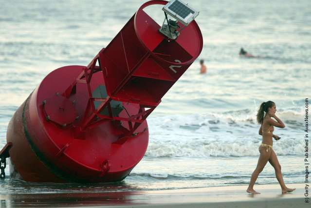 A beachgoer walks past a buoy that washed ashore after Hurricane Isabel made landfall in Virginia Beach, Virginia
