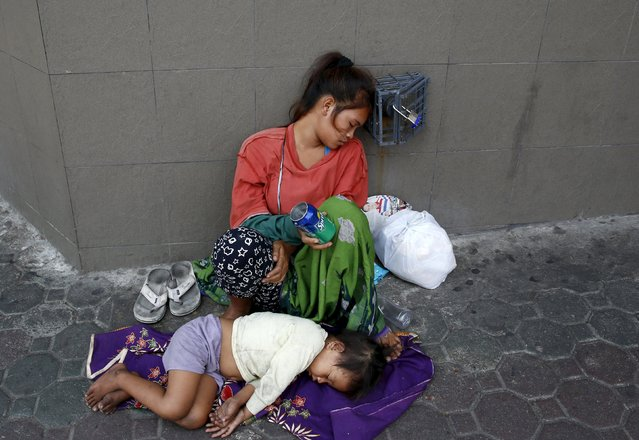 A mother and her child sleep along a sidewalk as they beg for money in the mountain resort of Baguio city in northern Philippines, April 16, 2016. (Photo by Erik De Castro/Reuters)