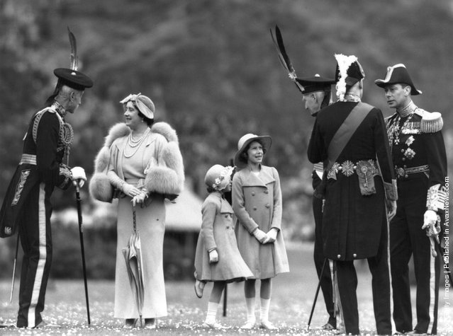 Queen Elizabeth talking to Lord Elphinstone during an inspection of the Royal Company of Archers at the Palace of Holyroodhouse, Edinburgh. Her husband King George VI  is on the right; Princesses Elizabeth and Margaret Rose are in the centre