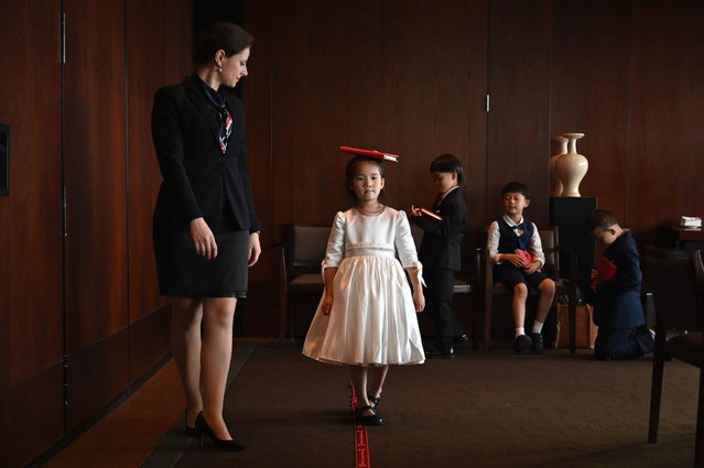 This picture taken on June 1, 2019 shows Miona Milakov (L) guiding Zoey Zhang on how to walk during an etiquette and manners class in central Shanghai. (Photo by Hector Retamal/AFP Photo)