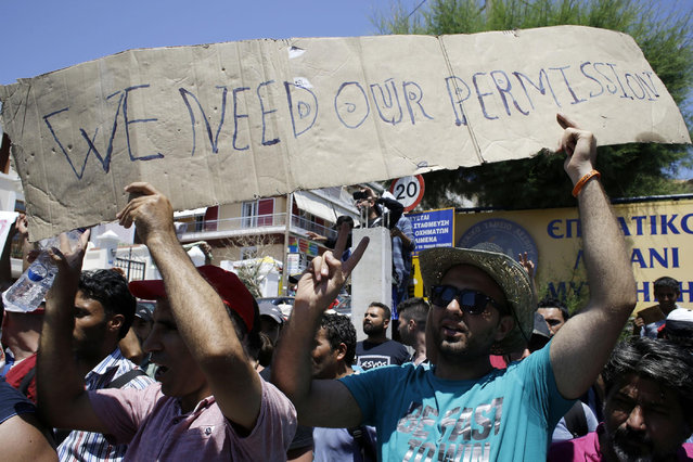 Syrians shout slogans during a protest by refugees and migrants, demanding better living conditions and faster processing of their asylum registrations at the port of Mytilene, on the northern Greek island of Lesvos on Wednesday, June 17, 2015. The Aegean island has borne the brunt of a huge influx of migrants from the Middle East, Asia and Africa crossing from Turkey to nearby Greek islands. More than 50,000 migrants have arrived in Greece so far this year. (AP Photo/Thanassis Stavrakis)