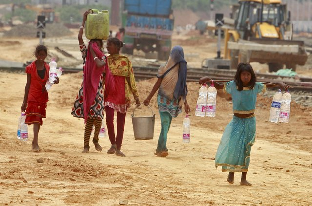 Young girls carry containers filled with drinking water beside the railway station in Agartala, India, April 20, 2016. (Photo by Jayanta Dey/Reuters)