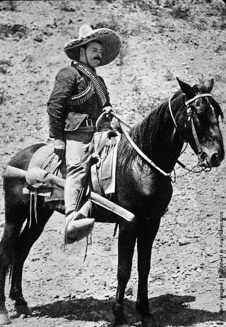 Mexican revolutionary Pancho Villa sits on horseback, wearing a straw hat and ammunition strapped across his shoulders, 1910s
