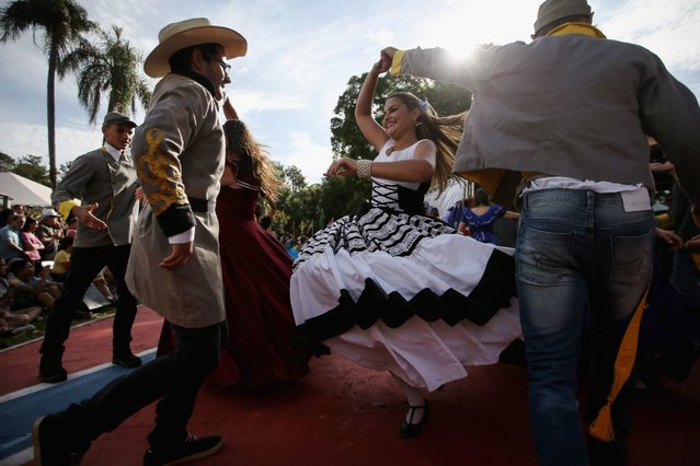 People dance in traditional outfits at the annual Festa Confederada, or Confederate Party, on April 24, 2016 in Santa Barbara d'Oeste, Brazil. The festival is put on by Brazilian descendants of families who fled from the southern United States to Brazil during Reconstruction, between 1865 and 1875, following the end of the U.S. Civil War. Thousands attend the festival which is held at the American Cemetery, or Cemiterio dos Americanos, where graves of settlers and descendants remain to this day. (Photo by Mario Tama/Getty Images)