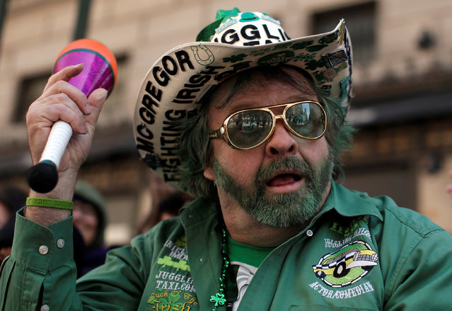 A paradegoer watches the St Patrick's Day parade on 5th Avenue in New York City, U.S., March 17, 2017. (Photo by Andrew Kelly/Reuters)