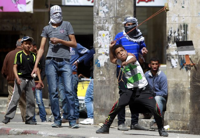 A Palestinian child uses a sling to hurl rocks toward Israeli soldiers during clashes in the West Bank city of Hebron, 16 April 2014. An Israeli policeman was shot dead on Passover night outside Hebron and today a large procession was held by Jewish settlers in the divided city of Hebron. Israeli police report 7 Palestinians wounded by rubber-coated steel bullets fired by police to disperse the crowd. (Photo by Abed Al Hashlamoun/EPA)