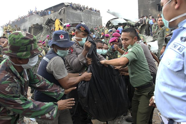Security forces and rescue teams remove the bodies of victims from the wreckage of an Indonesian military C-130 Hercules transport plane after it crashed into a residential area in the North Sumatra city of Medan, Indonesia, June 30, 2015, in this photo taken by Antara Foto