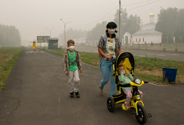 People, wearing masks to protect themselves from smoke of wildfires, walk along a street in the town of Ust-Ilimsk in Irkutsk Region, Russia on August 9, 2019. (Photo by Milena Pyankova/Reuters)