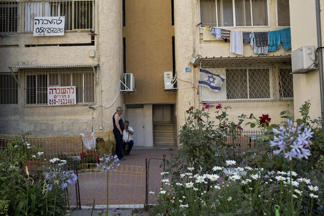 In this Monday, June 22, 2015, photo, Israelis sit at the entrance to their house at the southern Israeli town of Sderot, next to the Israel-Gaza border. (Photo by Oded Balilty/AP Photo)