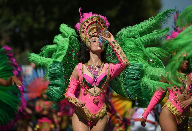 A performer in costume takes a drink of water during the carnival on the main Parade day of the Notting Hill Carnival in west London on August 26, 2019. (Photo by Daniel Leal-Olivas/AFP Photo)