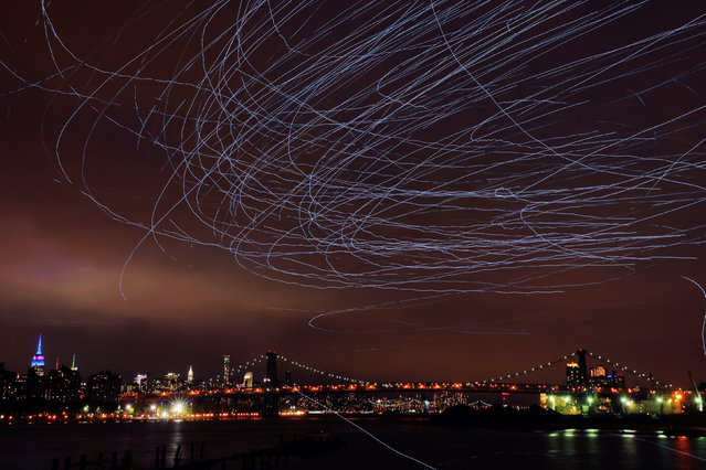 """LED lights attached to pigeons leave light trails in the sky while they fly as part of the """"Fly by Night"""" art installation by Duke Riley above the Brooklyn borough of New York, U.S.,May 5, 2016. (Photo by Lucas Jackson/Reuters)"""