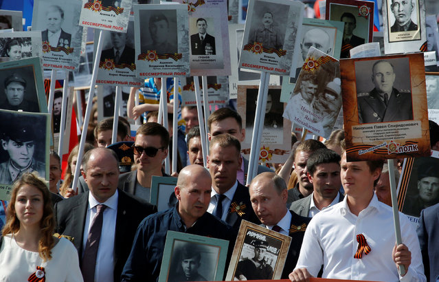 Russian President Vladimir Putin (C) holds the portrait of his father, war veteran Vladimir Spiridonovich Putin as he takes part in the Immortal Regiment march during the Victory Day celebrations, marking the 71st anniversary of the victory over Nazi Germany in World War Two, at Red Square in Moscow, Russia May 9, 2016. (Photo by Sergei Karpukhin/Reuters)