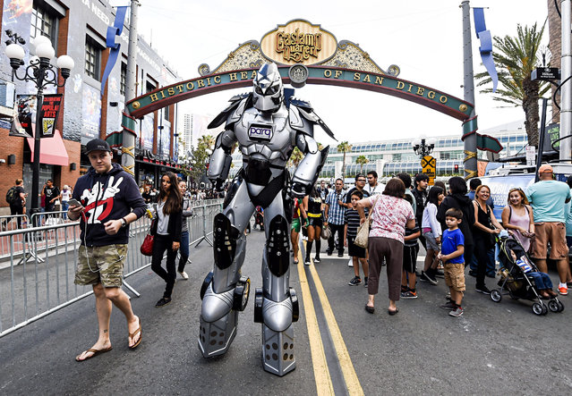 A fan in a huge robot costume towers over sightseers in the Gaslamp District on first day of the 2015 Comic-Con International held at the San Diego Convention Center Thursday, July 9, 2015 in San Diego. (Photo by Denis Poroy/Invision/AP Photo)