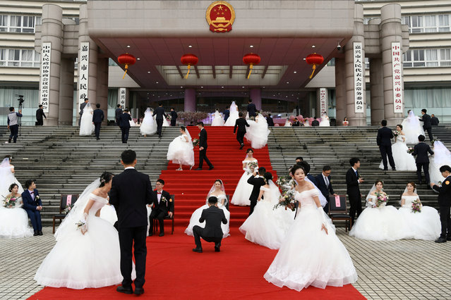Couples attend a mass wedding at the city's municipal government building ahead of the 70th founding anniversary of People's Republic of China in Jiaxing, Zhejiang province, China on September 22, 2019. (Photo by Reuters/China Stringer Network)