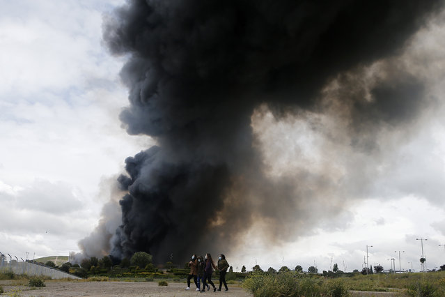 Four women walk with masks in front of billowing black smoke from a huge fire in Sesena, central Spain, Friday, May 13, 2016. (Photo by Paul White/AP Photo)