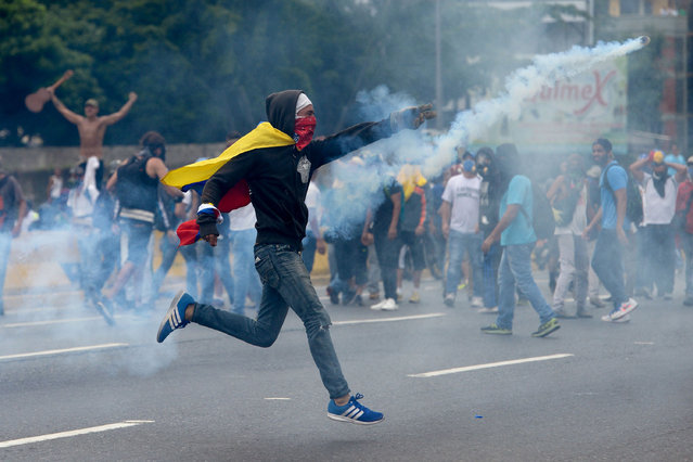 Demonstrators clash with the riot police during a protest against Venezuelan President Nicolas Maduro, in Caracas on April 20, 2017. (Photo by Federico Parra/AFP Photo)