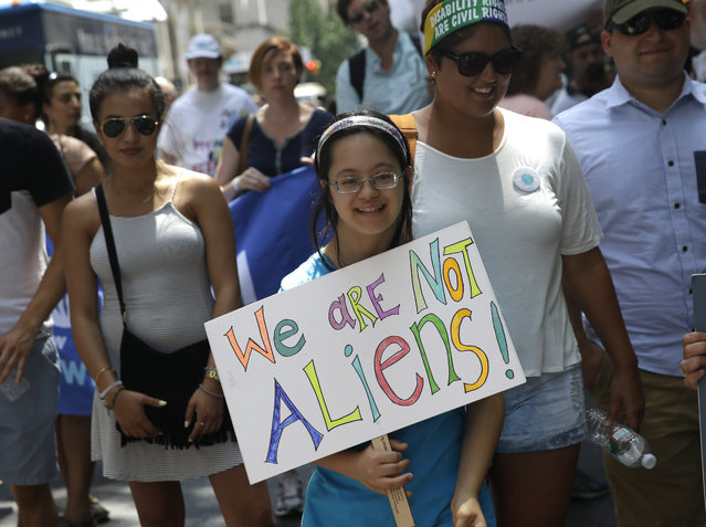Minal Rosenblum, of Montclair, N.J., holds a sign as she prepares to march in the inaugural Disability Pride Parade in New York, Sunday, July 12, 2015. (Photo by Seth Wenig/AP Photo)