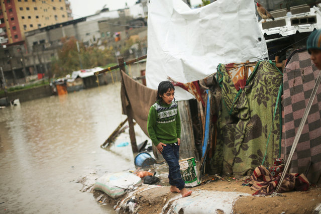 A Palestinian girl walks outside her family's flooded house following heavy rain in a neighbourhood in the northern Gaza Strip February 16, 2017. (Photo by Mohammed Salem/Reuters)