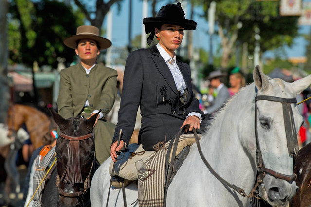 Participants in traditional dress ride on horseback as they enjoy the atmosphere at the Feria de Abril (April's Fair) on May 1, 2017 in Seville, Spain. (Photo by David Ramos/Getty Images)