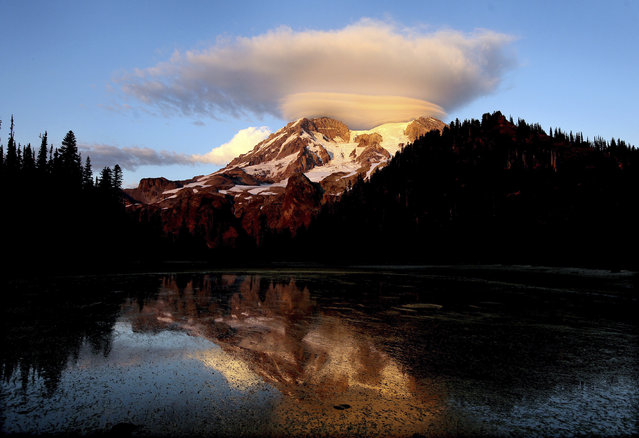 In this September 2012 file photo, a cloud hovers over Mount Rainier at sunset in a view from Klapatche Park Camp at Mount Rainier National Park, Wash. Access to Mount Rainer National Park and other national parks will be limited due to the government shutdown. (Photo by Drew Perine/The News Tribune via AP Photo)