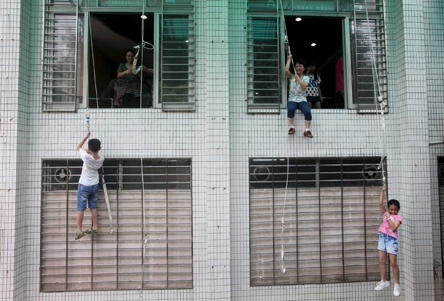Children and parents rope down a building as they participate in a safety education activity to experience a fire escape, at a school in Guangzhou, Guangdong province, July 5, 2015. The activity also prepares students with proper reactions to emergencies like traffic accidents and earthquakes, according to local media. (Photo by Reuters/Stringer)