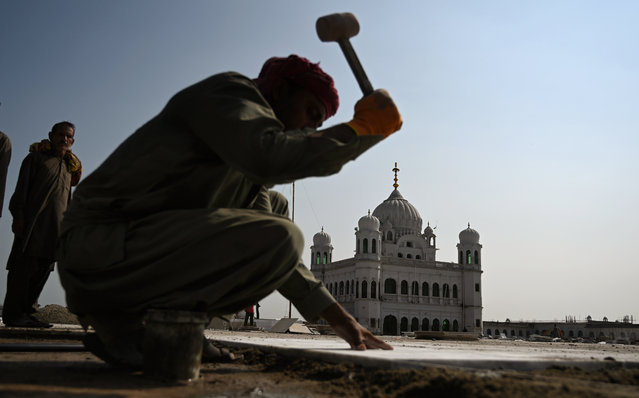 In this picture taken on September 16, 2019 men work on the construction site at the Sikh religious site Gurdwara Darbar Sahib, in the Pakistani town of Kartarpur near the Indian border. Pakistan on September 16 announced that the Kartarpur corridor will be opened for Indian Sikh pilgrims early this November. (Photo by Aamir Qureshi/AFP Photo)
