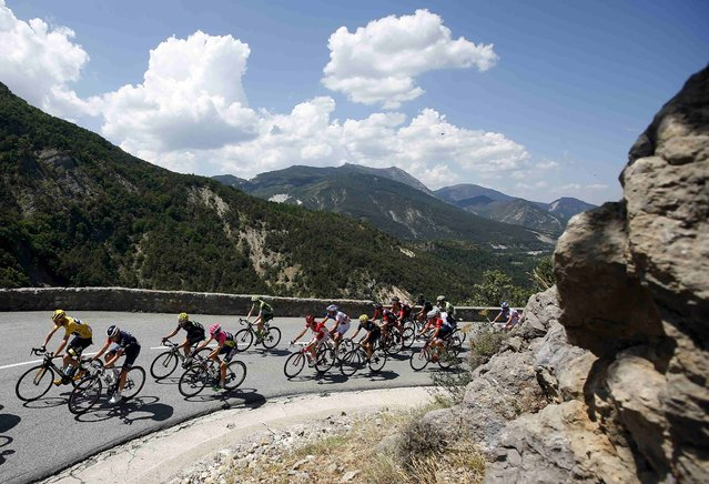 The pack of riders including Team Sky rider Chris Froome of Britain (L), race leader's yellow jersey, cycle during the 161-km (100 miles) 17th stage of the 102nd Tour de France cycling race from Digne-les-Bains to Pra Loup in the French Alps mountains, France, July 22, 2015. (Photo by Eric Gaillard/Reuters)