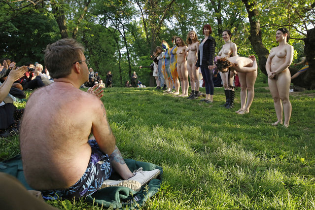 "A spectator wearing a bathing suit, left, watches as members of the mostly nude, all-female cast of the Outdoor Co-Ed Topless Pulp-Fiction Appreciation Society theater company take their bows following the company's production of Shakespeare's ""The Tempest"", in Central Park, Thursday, May 19, 2016, in New York. (Photo by Kathy Willens/AP Photo)"