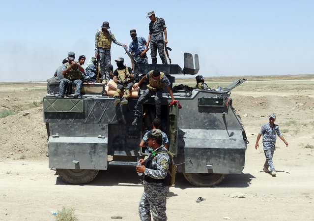 In this Thursday, July 23, 2015 photo, Iraqi federal police forces patrol in an eastern suburb of Ramadi, backed by Shiite and Sunni pro-government fighters and U.S.-led coalition airstrikes against Islamic State group positions in Anbar province, Iraq. (Photo by AP Photo)