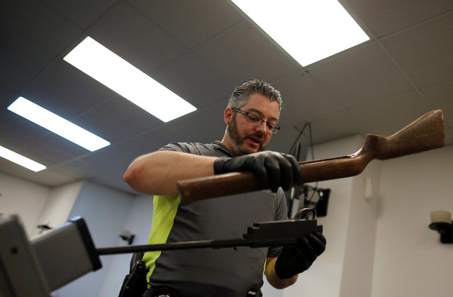 "A Chicago Police officers disassembles a replica gun turned in from the public as part of the ""Gun Turn-in"" event where a gift card is given for every firearm turned over to police at Universal Missionary Baptist Church in Chicago, Illinois, U.S. May 28, 2016. (Photo by Jim Young/Reuters)"
