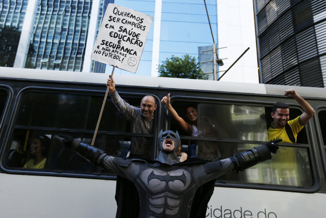 """An anti-government demonstrator dressed as Batman yells slogans accompanied by passengers on a bus, during a protest against the 2014 World Cup in Rio de Janeiro June 12, 2014. Placard reads """"We want to be the champions in healthcare, education and not just in football"""". (Photo by Pilar Olivares/Reuters)"""