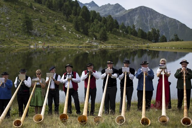Alpenhorn players perform along the Lac de Tracouet, situated 2200 meters (7220 feet) above sea level in Haute-Nendaz, canton of Valais, Switzerland, Sunday, July 26, 2015. (Photo by David Azia/AP Photo)