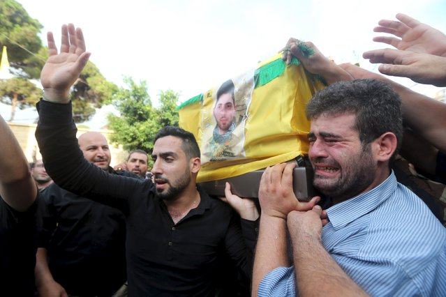 Lebanon's Hezbollah members and supporters react as they carry the coffin of Hezbollah fighter Mustapha al-Hooli in Beirut's southern suburbs July 28, 2015. The fighter was killed during what activists said were clashes between Hezbollah fighters alongside the army of Syria's President Bashar al-Assad against Syrian rebels in Syria. (Photo by Hasan Shaaban/Reuters)