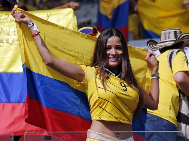 A Colombian supporter smiles as she waits for the start of the group C World Cup soccer match between Colombia and Greece at the Mineirao Stadium in Belo Horizonte, Brazil, Saturday, June 14, 2014. (Photo by Jon Super/AP Photo)