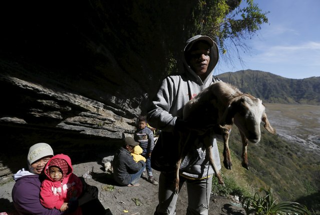 A Hindu villager holds his goat for offering as holy water is collected from a stream for prayers ahead of the annual Kasada festival at Mount Bromo in Indonesia's East Java province, July 31, 2015. (Photo by Reuters/Beawiharta)