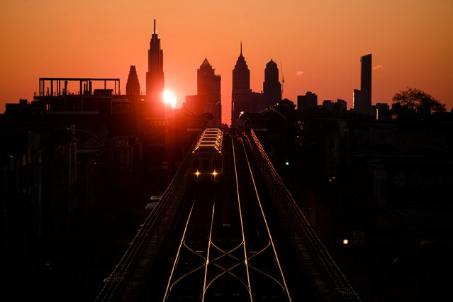 A train heads west as the sun rises from behind the city skyline in Philadelphia, Wednesday, March 6, 2019. The Southeastern Pennsylvania Transportation Authority said members of the Fraternal Order of Transit Police Lodge 109 walked off the job Wednesday. (Photo by Matt Rourke/AP Photo)